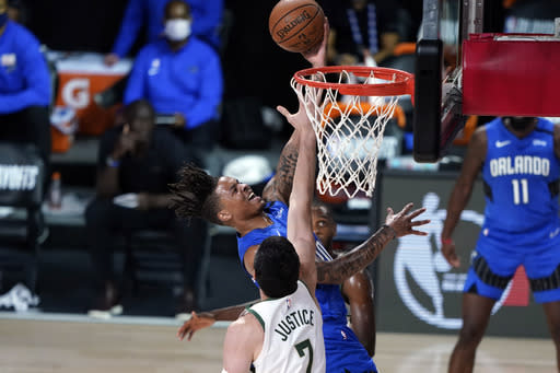 Orlando Magic's Markelle Fultz, top, goes up for a shot as Milwaukee Bucks' Ersan Ilyasova (7) defends during the second half of an NBA basketball first round playoff game Saturday, Aug. 29, 2020, in Lake Buena Vista, Fla. (AP Photo/Ashley Landis)