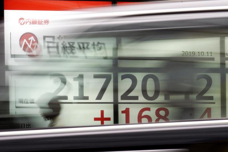 A woman walks past an electronic stock board showing Japan's Nikkei 225 index at a securities firm in Tokyo Friday, Oct. 11, 2019. Asian stock markets followed Wall Street higher Friday on optimism about U.S.-Chinese talks on ending a tariff war. (AP Photo/Eugene Hoshiko)