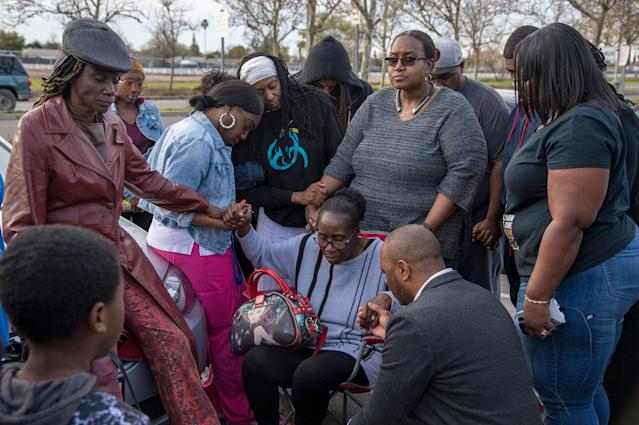 <p>Mar 19, 2018 – Sacramento, California, U.S. – Sequita Thompson, grandmother of Stephan Clark, is surrounded by family as they pray in the parking lot of the Meadowview Light Rail Station, in Sacramento, Calif., on March 19, 2018. Clark was killed by police the night of March 18, in the backyard of his grandmother's home. (Photo: Jose Luis Villegas/Sacramento Bee via ZUMA Wire) </p>