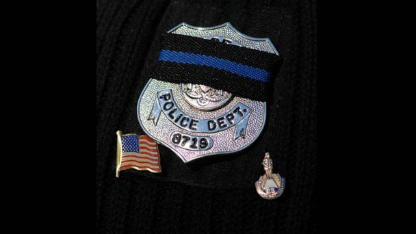 PHOTO: In this Nov. 7, 2007, file photo, a police officer wears a black ribbon on his badge at the funeral for a fellow officer in Philadelphia. (William Thomas Cain/Getty Images, FILE)