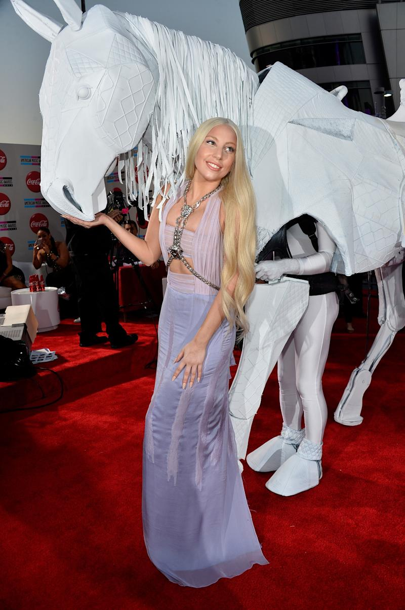 """Lady """"Godiva"""" Gaga arriving on the American Music Awards red carpet atop a mechanical horse and wearing Atelier Versace."""