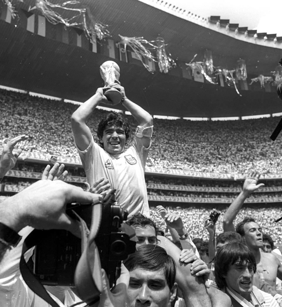 Argentine star Diego Maradona holds up the World Cup trophy as he is carried off the field after Argentina defeated West Germany 3-2 to win the World Cup soccer championship in Mexico City June 29, 1986. REUTERS/Gary Hershorn  AS