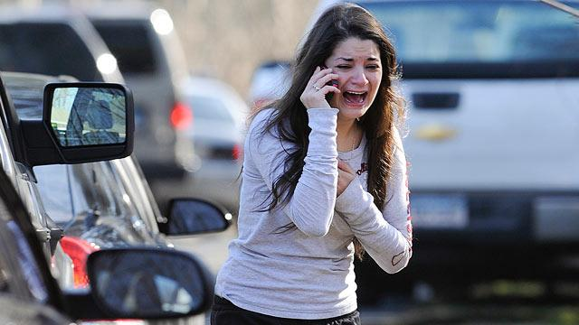 A woman waits to hear about her sister, a teacher, following a shooting at the Sandy Hook Elementary School in Newtown, Conn., about 60 miles northeast of New York City, Dec. 14, 2012. Credit: Jessica Hill/AP Photo