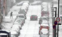 Parking cars are covered with snow during heavy snowfall in Gelsenkirchen, Germany, Sunday, Feb. 7, 2021. Snow falls extremely seldom in the industrial Ruhr area. (AP Photo/Martin Meissner)