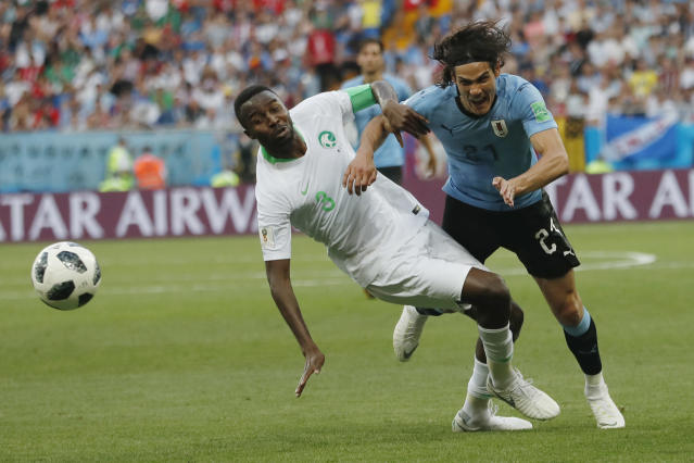 Uruguay's Edinson Cavani, right, and Saudi Arabia's Osama Hawsawi challenge for the ball during for the group A match between Uruguay and Saudi Arabia at the 2018 soccer World Cup in Rostov Arena in Rostov-on-Don, Russia, Wednesday, June 20, 2018. (AP Photo/Darko Vojinovic)