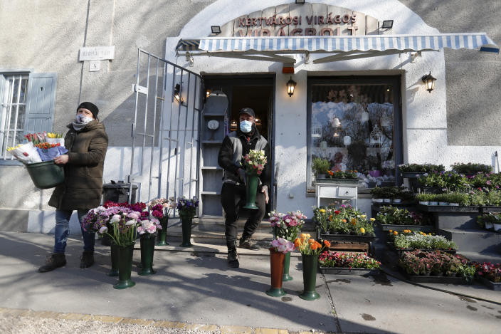 Staff members of a flower shop place flowers on the street in Budapest, Hungary, Wednesday April 7, 2021. Hungary's government lifted several lockdown restrictions on Wednesday, even as some doctors and medical experts urged caution after a record-breaking day of COVID-19 deaths, a move that came as Hungary reached 2.5 million first-dose vaccinations, a benchmark the government set for when a gradual reopening could move forward. (AP Photo/Laszlo Balogh)