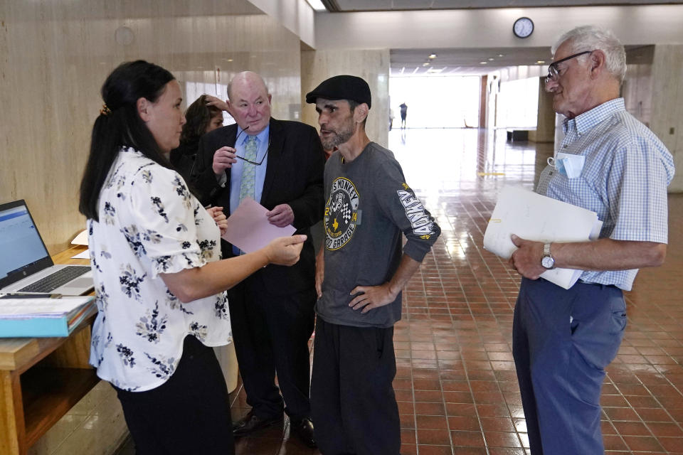 Kate Barrington, a rent relief case manager from Crossroads Rhode Island, left, talks with Luis Vertentes, a tenant from East Providence, R.I., second from right, during a meeting prior to an eviction hearing, Monday, Aug. 2, 2021, in Providence. Rhode Island tenants facing eviction after the lifting of a federal moratorium on being ousted for unpaid rent plead their case in court. Vertentes agreed to leave his residence, which he has not paid rent on in four months, in about three weeks. At right is landlord Roy Loiselle, second from left, is attorney Murray Gereboff. (AP Photo/Charles Krupa)
