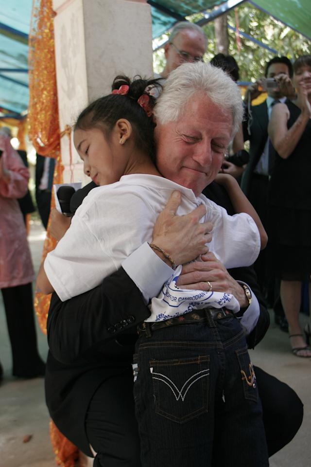 Former President Clinton embraces Towry, an HIV-positive girl who now lives at the New Hope for Cambodian Children orphanage, while on a field visit to Cambodia in December 2006. Towry is one of more than 305,000 children in 34 countries who have received lifesaving antiretroviral (ARV) treatment under Clinton Foundation programs.<br><br>(Photo credit: David Scull/Clinton Foundation)