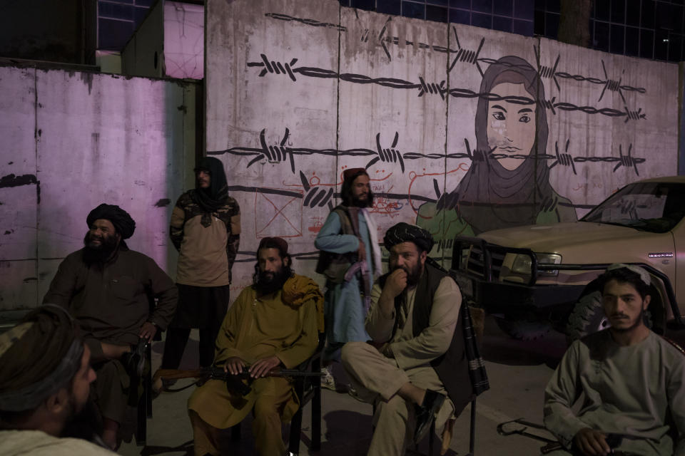 Taliban members sit in front of a mural depicting a woman behind barbed wire in Kabul, Afghanistan, Tuesday, Sept. 21, 2021. (AP Photo/Felipe Dana)