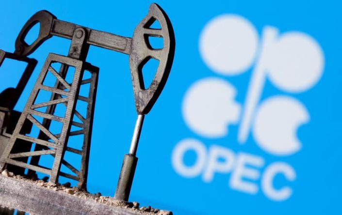 uFILE PHOTO: A 3D printed oil pump jack in front of the OPEC logo