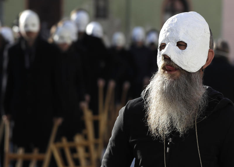 Participants dressed in black, wearing masks, beating drums and pushing small carts that make a synchronized and loud sound take part in an Easter procession through the streets of Ceske Budejovice, Czech Republic, Friday, April 19, 2019. (AP Photo/Petr David Josek)