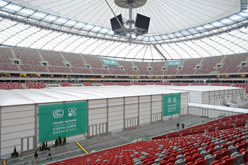 People walk past special halls set on the pitch of the National Stadium, the venue of the U.N. Climate Change Conference, in Warsaw, Poland, Sunday, Nov. 10, 2013. Climate envoys from rich countries, emerging economies and low-lying nations at risk of being swamped by rising seas will meet in Poland Monday for the next two weeks to lay the groundwork for a new global warming pact. (AP Photo/Alik Keplicz)