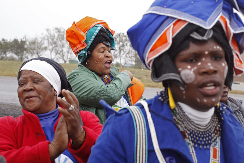 Woman sing in honor of former President Nelson Mandela in front of his house in Qunu, South Africa, Thursday, July 4, 2013. In a macabre family feud fought as Nelson Mandela remained in critical condition, a South African court ruled Wednesday that the former president's grandson must return the bodies of the 94-year-old's three deceased children to their original burial site. (AP Photo/Schalk van Zuydam)