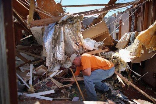 A man salvages items from what was the living room of his home after it was damaged by a tornado on June 2, 2013 in El Reno, Oklahoma. A series of tornadoes battered Oklahoma with high winds, heavy rain and large hail, causing at least 11 fatalities in a state already reeling from a monster twister that claimed two dozen lives last month