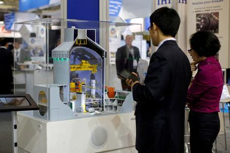 FILE PHOTO - Visitors look at a nuclear power plant station model by American company Westinghouse at the World Nuclear Exhibition 2014 in Le Bourget