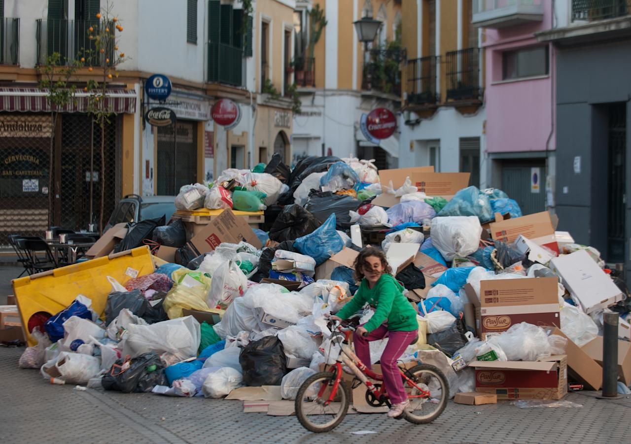 A young girl rides her bike past a mound of garbage during the ninth day of the Seville waste disposal strike on February 5, 2013 in Seville, Spain. Workers are striking over demands they take a 5% pay cut and extend their working week to 37.5 hours.  (Photo by Denis Doyle/Getty Images)