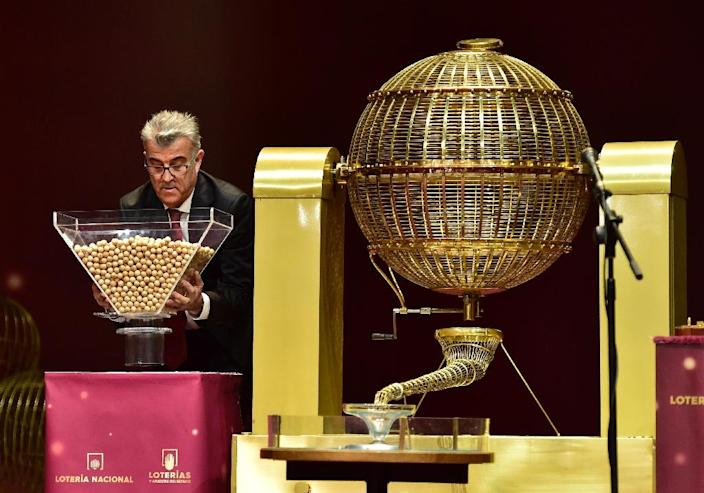 """An official prepares the balls with the numbers before the draw of Spain's Christmas """"El Gordo"""" lottery in Madrid, on December 22, 2016 (AFP Photo/GERARD JULIEN)"""