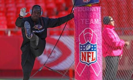 A player warms up next to a Kansas City Chiefs field goal post outfitted with special pink padding in honor of Breast Cancer Awareness month.