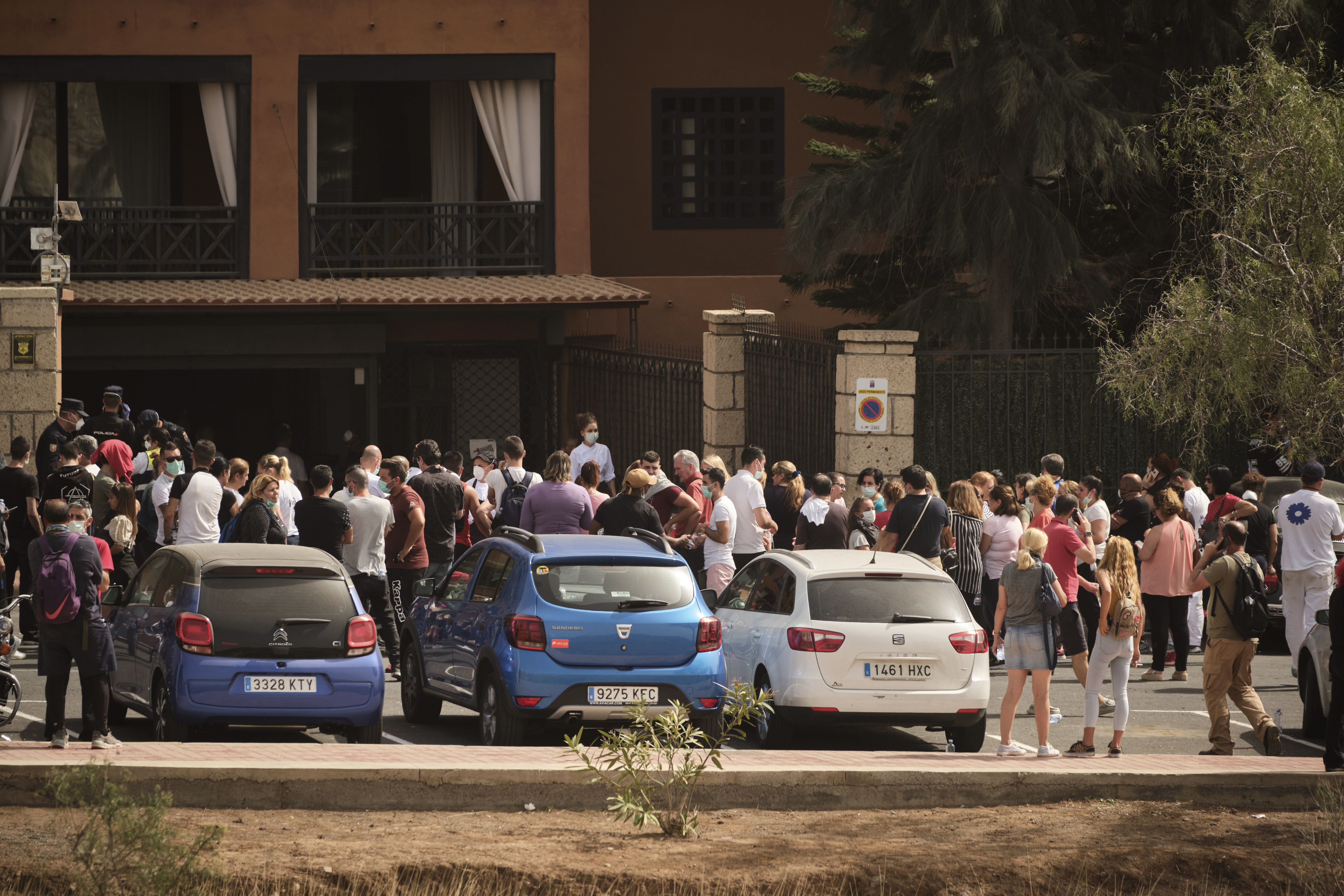 Hotel workers queue to get tested at the H10 Costa Adeje Palace hotel in the Canary Island of Tenerife, Spain, Tuesday, Feb. 25, 2020. Spanish officials say a tourist hotel on the Canary Island of Tenerife has been placed in quarantine after an Italian doctor staying there tested positive for the COVID-19 virus and Spanish news media says some 1,000 tourists staying at the complex are not allowed to leave. (AP Photo)