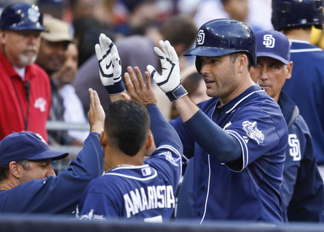San Diego Padres' Seth Smith high-fives teammates after his solo home run against the New York Mets in the sixth inning of a baseball game Saturday, July 19, 2014, in San Diego. (AP Photo/Lenny Ignelzi)