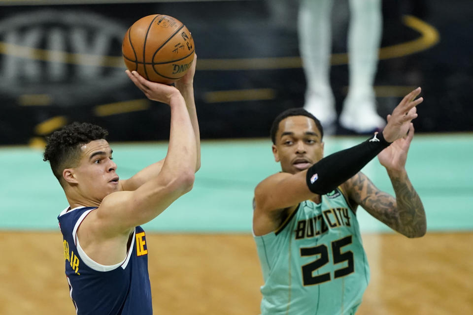Denver Nuggets forward Michael Porter Jr. scores as Charlotte Hornets forward P.J. Washington looks on during the first half of an NBA basketball game on Tuesday, May 11, 2021, in Charlotte, N.C. (AP Photo/Chris Carlson)