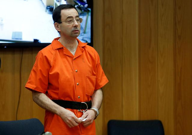 FILE PHOTO: Larry Nassar, a former team USA Gymnastics doctor who pleaded guilty in November 2017 to sexual assault charges, stands in court during his sentencing hearing in the Eaton County Court in Charlotte, Michigan, U.S., February 5, 2018. REUTERS/Rebecca Cook/File Photo