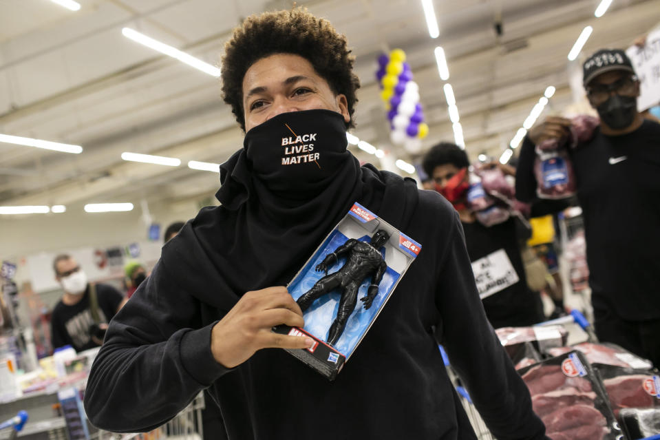 A Black Lives Matter activist holds a Black Panther doll inside a Carrefour supermarket during a demonstration against the murder of Black man Joao Alberto Silveira Freitas at a different Carrefour the night before, on Brazil's National Black Consciousness Day in Rio de Janeiro, Brazil, Friday, Nov.20, 2020. Freitas died after being beaten by supermarket security guards in the southern Brazilian city of Porto Alegre, sparking outrage as videos of the incident circulated on social media. (AP Photo/Bruna Prado)