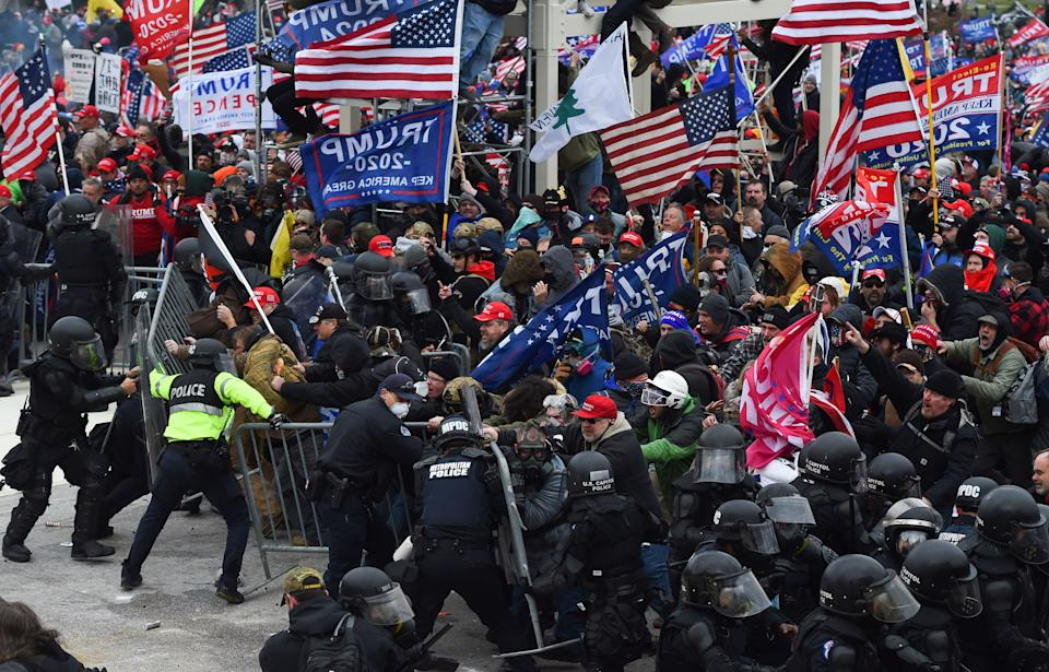 Trump supporters clash with police and security forces as they push barricades to storm the US Capitol in Washington D.C on January 6, 2021. - Demonstrators breeched security and entered the Capitol as Congress debated the a 2020 presidential election Electoral Vote Certification. (Photo by ROBERTO SCHMIDT / AFP) (Photo by ROBERTO SCHMIDT/AFP via Getty Images)