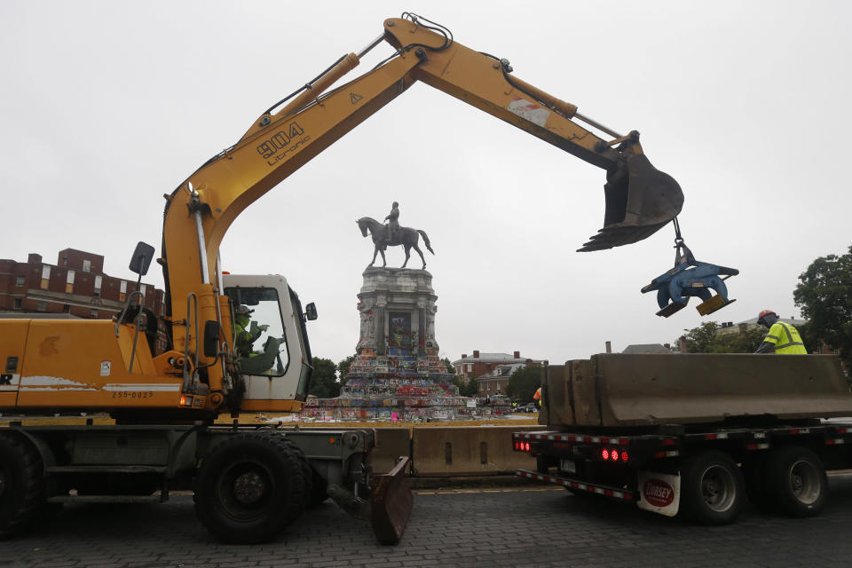 Workers for The Virginia Department of General Services install concrete barriers around the statue of Confederate General Robert E. Lee on Monument Avenue Wednesday, June 17, 2020, in Richmond, Va. The barriers are intended to protect the safety of demonstrators as well as the structure itself. (AP Photo/Steve Helber)