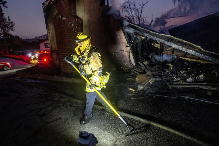 Firefighter Jesse Sparks mops up at a destroyed home as the Hillside Fire burns in San Bernardino, Calif., on Thursday, Oct. 31, 2019. Whipped by strong wind, the blaze destroyed multiple residences. (AP Photo/Noah Berger)
