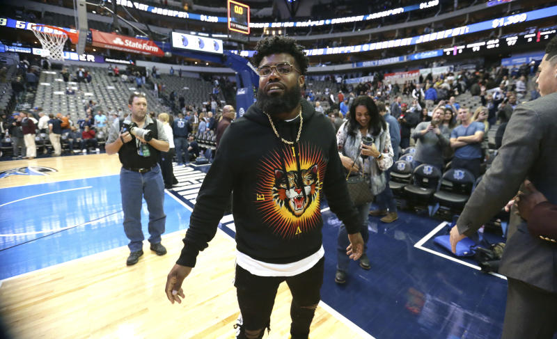 Dallas Cowboys running back Ezekiel Elliott walks the floor after an NBA basketball game between the Phoenix Suns and Dallas Mavericks in Dallas, Monday, Dec. 18, 2017.(AP Photo/LM Otero)