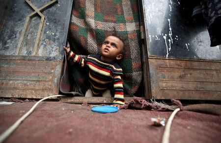 FILE PHOTO: A displaced child from Yemen's Red Sea port city of Hodeida looks out from the door of his family's shelter in Sanaa, Yemen May 12, 2019. REUTERS/Khaled Abdullah/File Photo