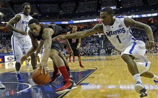 Memphis guard Joe Jackson (1) tries to steal the ball from Louisville center Zach Price (25) during the first half of an NCAA college basketball game on Saturday, Dec. 15, 2012, in Memphis, Tenn. (AP Photo/Lance Murphey)