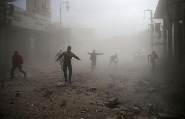 <p>Civil defence members and civilians are seen running after an air raid in the besieged town of Douma in eastern Ghouta in Damascus, Syria, Feb. 6, 2018. (Photo: Bassam Khabieh/Reuters) </p>