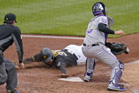 Pittsburgh Pirates' Will Craig, center, scores ahead of a tag by Colorado Rockies catcher Dom Nunez, right, on a groundout to first by Adam Frazier during the fourth inning of a baseball game in Pittsburgh, Sunday, May 30, 2021. Umpire D.J. Rayburn, left, makes the call on the play. (AP Photo/Gene J. Puskar)