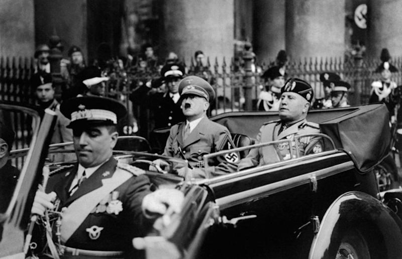 A picture taken in September 1937, in Munich, shows German Chancellor Adolf Hitler (R) riding in a car with Italian dictator Benito Mussolini while the crowd gives the fascist salute. AFP PHOTO / FRANCE PRESSE VOIR (Photo credit should read -/AFP/Getty Images)