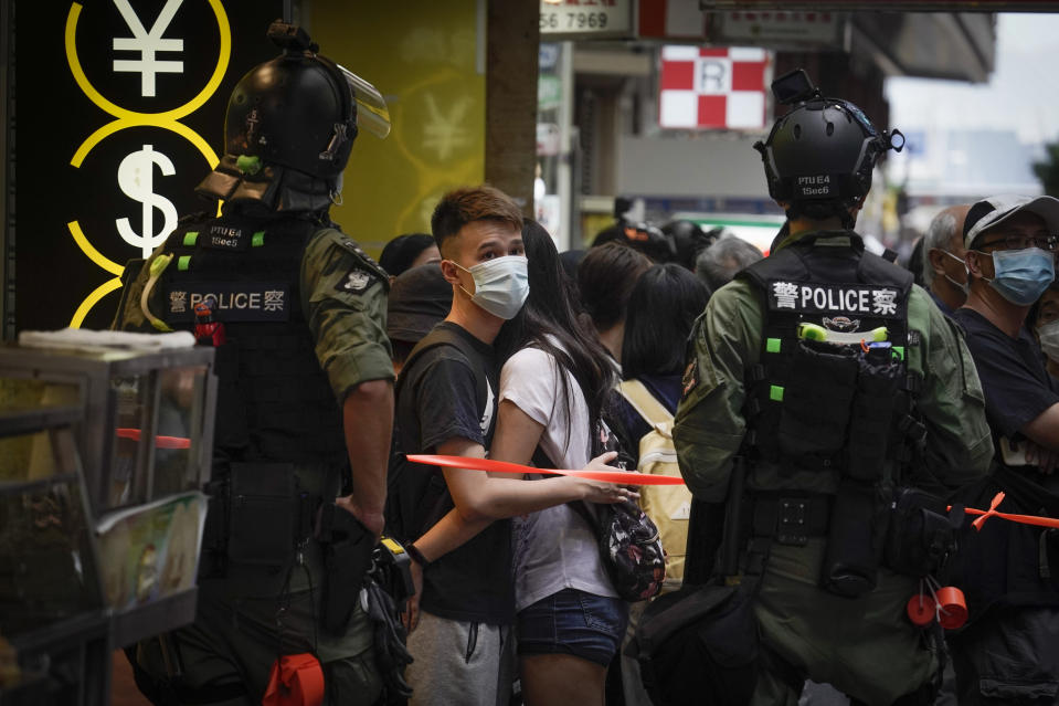 Pedestrians are stopped by police for checking on China's National Day in Causeway Bay, Hong Kong, Thursday, Oct. 1, 2020. A popular shopping district in Causeway Bay saw a heavy police presence after online calls urged people to join protests. (AP Photo/Kin Cheung)