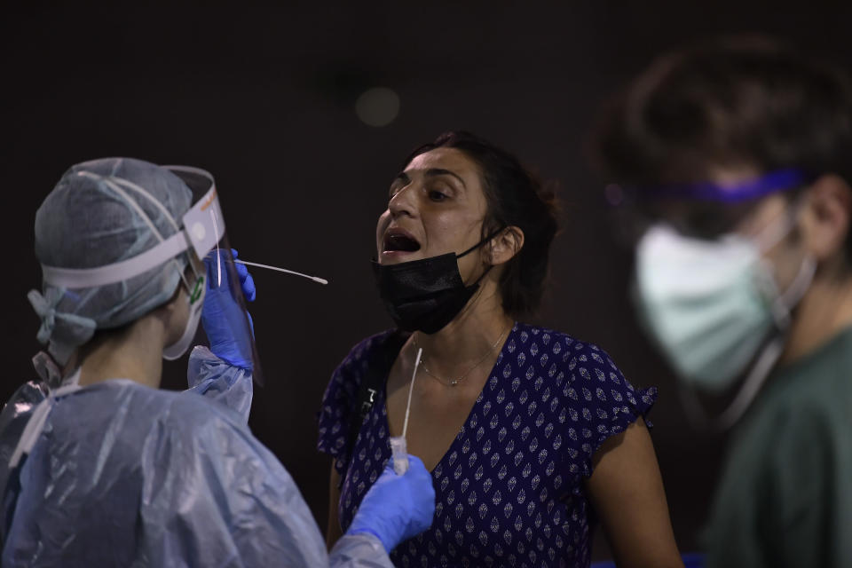 A health worker takes a swab from a teenager during a rapid antigen test for COVID-19 in Pamplona, northern Spain, Monday, July 5, 2021. During the last three days local authorities have called on teenagers to be tested due to the increase of people in the town contracting coronavirus after returning from vacations in the small village of Salou, northeast of Spain. (AP Photo/Alvaro Barrientos)