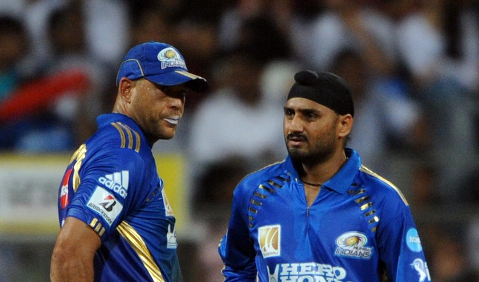 Former Mumbai Indians cricketers Andrew Symonds (L) and Harbhajan Singh discuss during a IPL Twenty20 match.