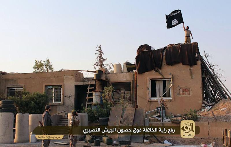 An image made available by Jihadist media outlet Welayat Raqa on July 25, 2014, allegedly shows members of the Islamic state militant group raising their flag over a building belonging to a Syrian army base in Raqa