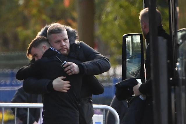 English midfielder James Maddison (L) embraces a member of the security team (Photo by Mike Egerton/PA Images via Getty Images)