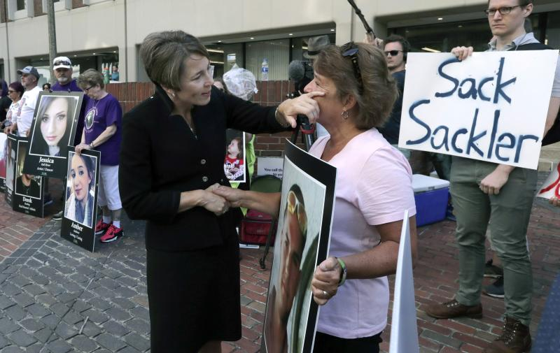FILE - In this Aug. 2, 2019, file photo, Massachusetts Attorney General Maura Healey, left, wipes a tear from the face of Wendy Werbiskis, of East Hampton, Mass., one of the protesters gathered outside a courthouse in Boston, where a judge was to hear arguments in the state's lawsuit against Purdue Pharma over its role in the national drug epidemic. Reports emerging about a possible financial settlement with Purdue, the company that has come to symbolize the nation's opioid epidemic, suggests the settlement amount won't come anywhere near what the national crisis has cost. (AP Photo/Charles Krupa, File)