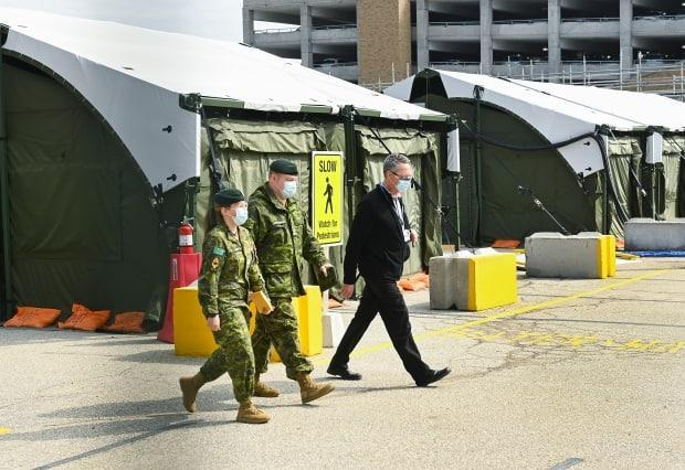 Military health-care personnel prepare for patients at a mobile unit at Toronto's Sunnybrook Hospital, a priority site because of 'urgent staffing needs' during the pandemic. (Nathan Denette/The Canadian Press - image credit)