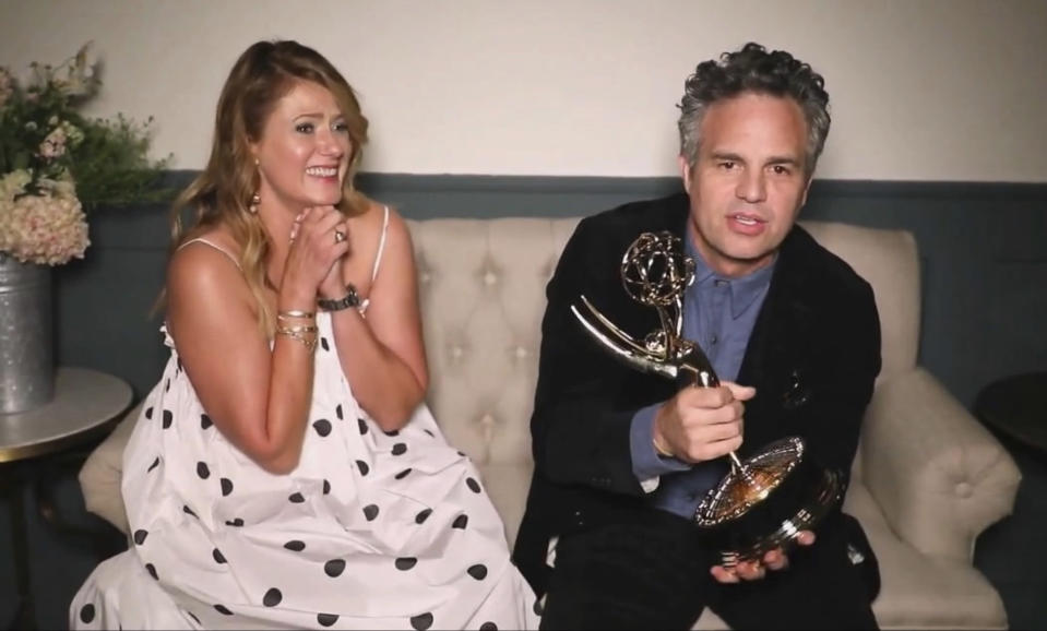"In this video grab captured on Sept. 20, 2020, courtesy of the Academy of Television Arts & Sciences and ABC Entertainment, Mark Ruffalo accepts the award for outstanding lead actor in a limited series or movie for ""I Know this Much is True"" during the 72nd Emmy Awards broadcast. Looking on at left is Ruffalo's wife Sunrise Coigney. (The Television Academy and ABC Entertainment via AP)"