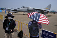 A man carrying an umbrella with the United States flag colors look at Chinese military's JH-7A2 fighter bomber during the 13th China International Aviation and Aerospace Exhibition, also known as Airshow China 2021 on Sept. 28, 2021 in Zhuhai in southern China's Guangdong province. Nine months into U.S. President Joe Biden's administration, there are signs of movement in what has been a fraught U.S.-China relationship. (AP Photo/Ng Han Guan)