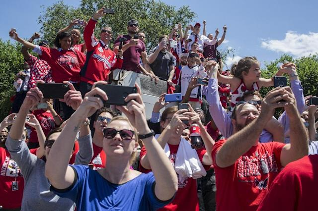 Fans take pictures as the Stanley Cup-winning Washington Capitals parade down Constitution Avenue (AFP Photo/Zach Gibson)
