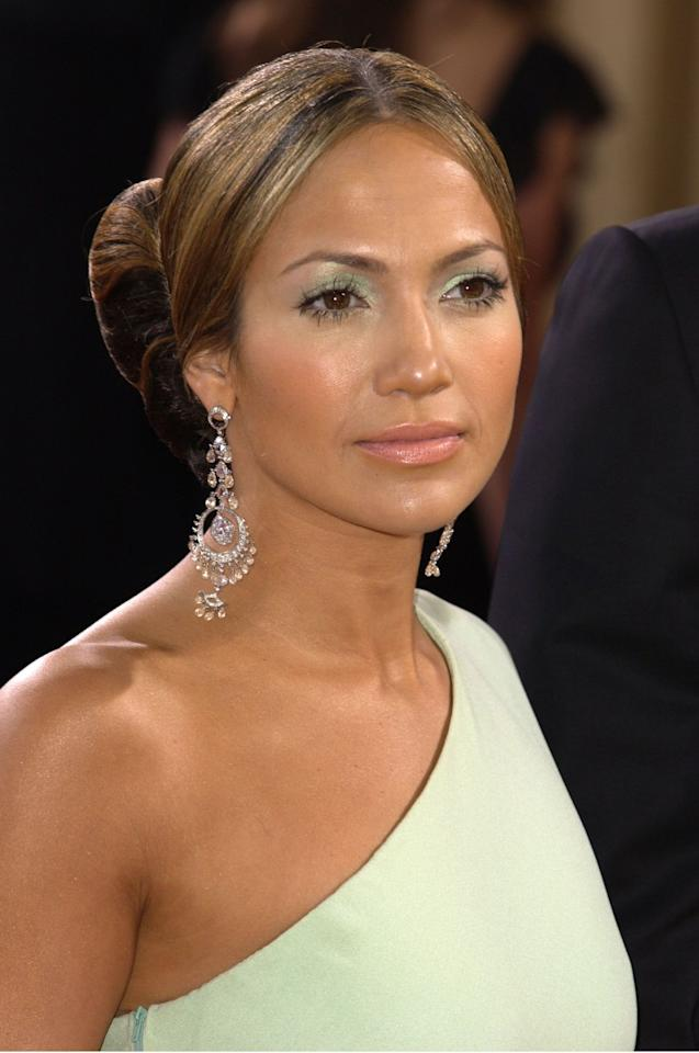 <p>Jennifer Lopez's sleek and sculptural updo was the perfect pairing for her unusual minty green eyeshadow and coral-pink lipstick in 2003. </p>