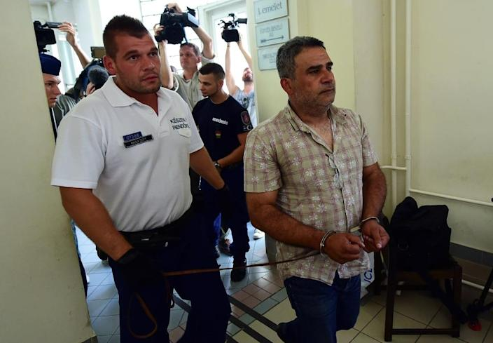 One of four suspects in the Austrian motorway migrant tragedy are led by a Hungarian police official (centre) into the Kecskemet courtroom in Kecskemet, Hungary on August 29, 2015 (AFP Photo/Attila Kisbenedek)
