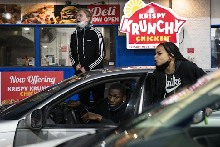 People in and around a car at a gas station look alarmed.