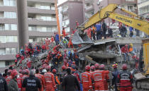 Rescue workers, who were trying to reach survivors in the rubble of a collapsed building, leave the area as the adjacent building at the right started moving, in Izmir, Turkey, Sunday, Nov. 1, 2020. Rescue teams continue ploughing through concrete blocs and debris of collapsed buildings in Turkey's third largest city in search of survivors of a powerful earthquake that struck Turkey's Aegean coast and north of the Greek island of Samos, Friday Oct. 30, killing dozens. Hundreds of others were injured.(AP Photo/Ismail Gokmen)